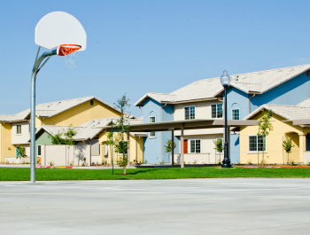 A basketball court with houses in the background.