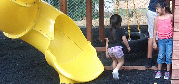 A little girl approaches a tire swing on a playground with a yellow slide
