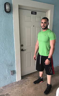 A disabled man wearing a green shirt and black track pants stands in front of his new home