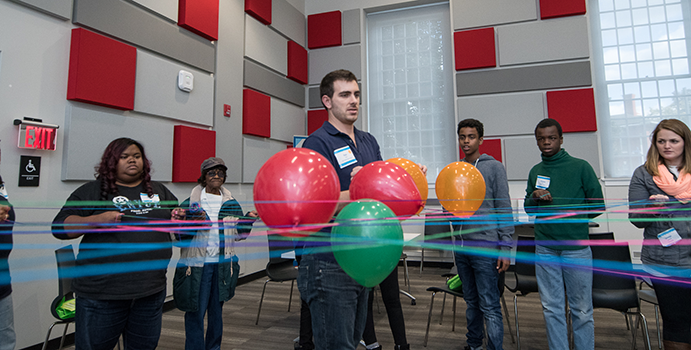 A teacher hosts an experiment with balloons with resident youth