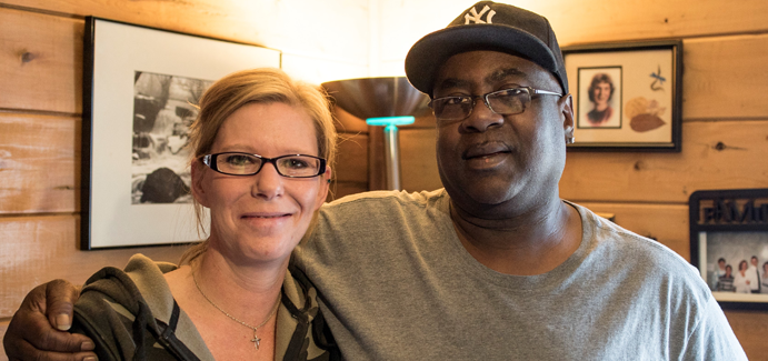A black man wearing eyeglasses and a New York baseball cap stands next to a whie woman wearing eyeglasses in a log cabin