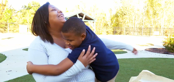 A black mother sitting outside catches her son in a hug