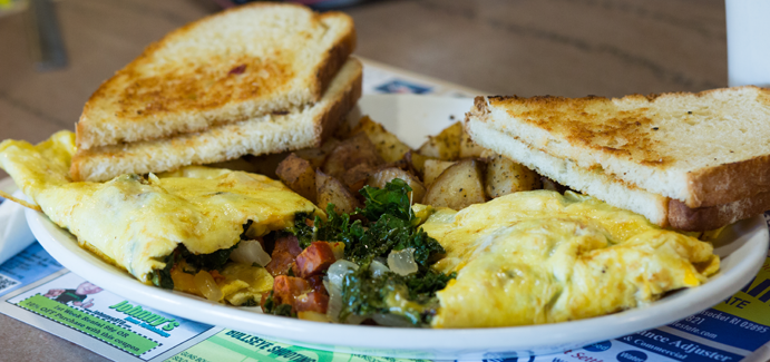 Four slices of toast, fried potatoes and a spinach-onion omelette featured on a bar