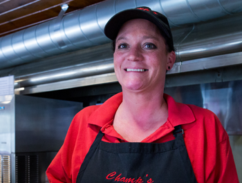 "A woman wearing a red shirt with text that reads ""Champ's diner"""