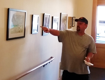 A white man wearing a black baseball cap and t-shirt points at a photograph on a beige wall