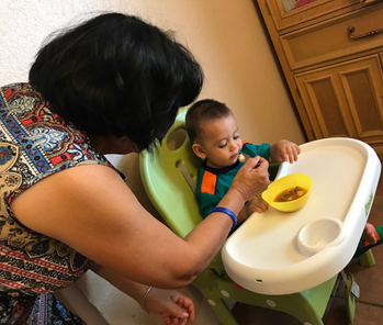 A woman feeds a baby sitting in a high chair