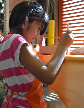 A young girl wearing a pink and white striped shirt paints a birdhouse