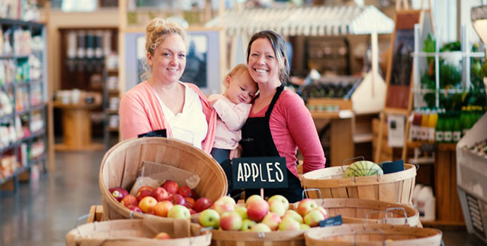 A white woman wearing a pink cardigan and white shirt stands next to another white woman holding a baby in front of a barrel of apples