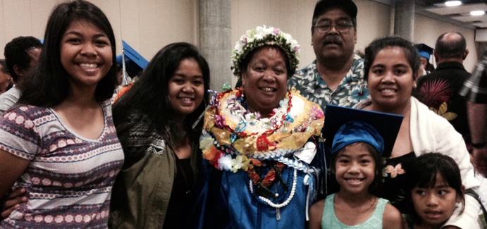 Hawaiian woman stands with her family at her graduation