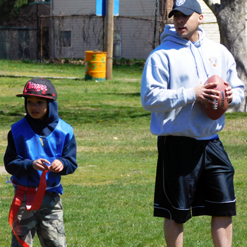 A local police officer holds a football next to a local kid wearing a red flag