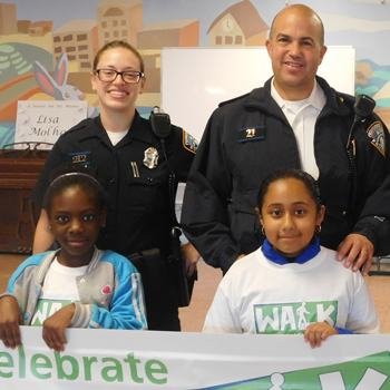 "Office Tracie Miller and Lt. Richard Fernandes stand behind Olneyville youth holding up a ""celebrate"" sign"