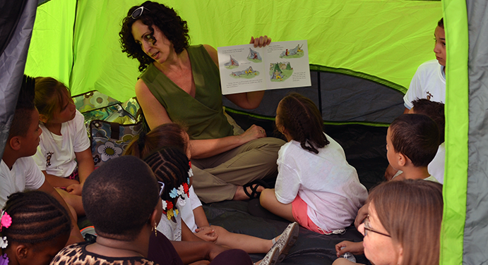 A woman wearing a green tank top reads to a mixed group of children in a neon green and slate gray tent