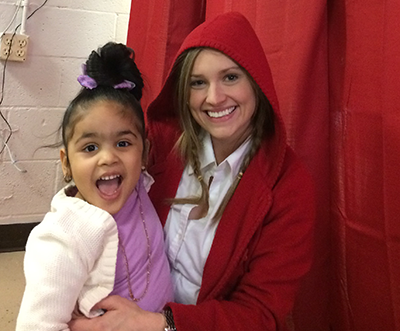 A girl sitting next to a woman wearing a red hood grins at the camera