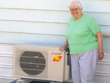 Elderly white woman stands next to her new HVAC unit