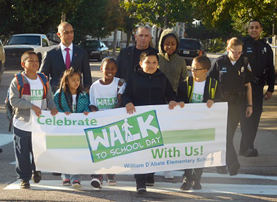 "A group of kids carrying a ""Celebrate Walk to School Day"" banner walk with school and city officials"