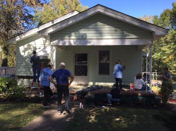 Men and women work on repairing a home