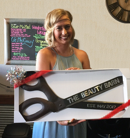 A white woman holds a pair of large scissors that say The Beauty Barn