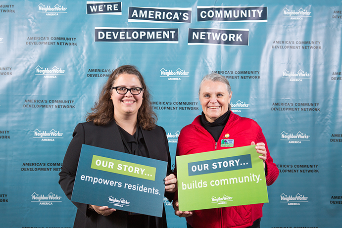 Sheila Rice stands in front of a banner that says We're America's Community Development Network